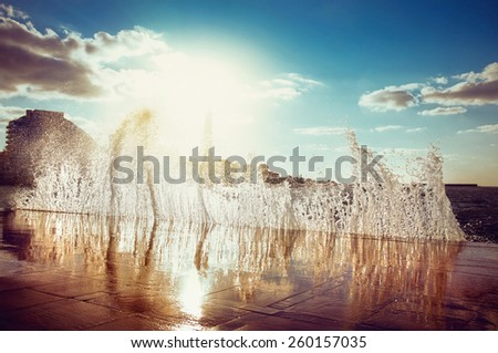 waves at sunset on the waterfront - stock photo