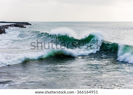 """Waves break at unusual angles at the """"wedge"""", as rebound waves collide with oncoming waves outside the breakwall of Los Angeles Harbor at Cabrillo Beach in San Pedro, California.  - stock photo"""