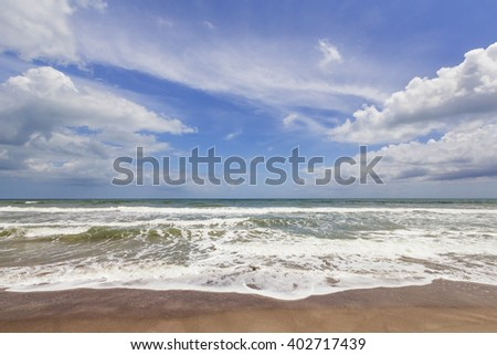 Waves break gently on a sandy beach with beautiful clouds in a deep blue sky over aqua waters. - stock photo