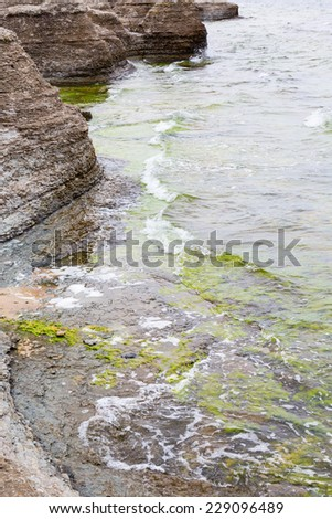 Waves breaking at the sea stack shore - stock photo