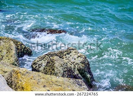 Waves breaking on a stony beach. - stock photo