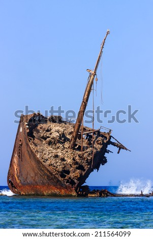 Waves breaking on an old, rusting ship wreck abandoned on a coral reef - stock photo