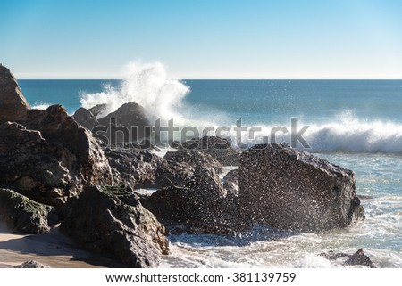 waves breaking on rocks at point dume, california - stock photo