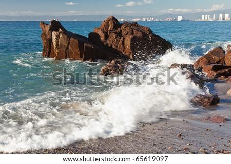 Waves breaking on the rocks of Banderas Bay, Puerto Vallarta, Mexico - stock photo