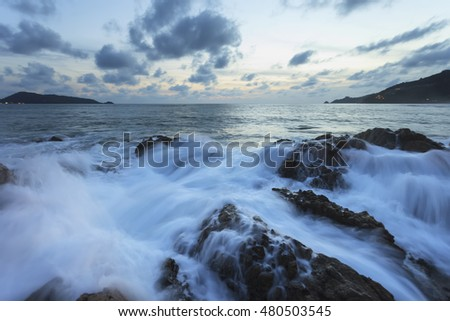 Waves breaking on the rocks sunset beach (Kalim beach Phuket)