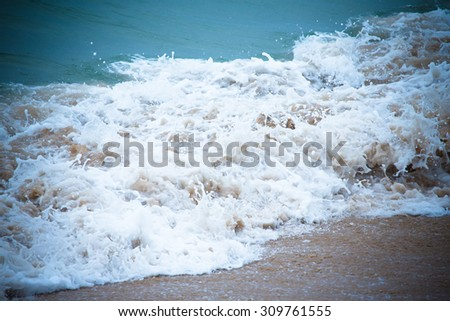 Waves breaking on the shore and transformed into a foam. Selective focus. Tinted - stock photo