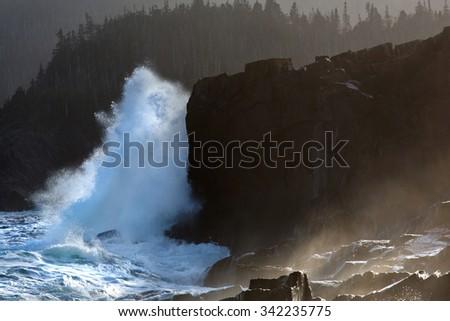 Waves breaking over rocks along the Newfoundland coastline. - stock photo