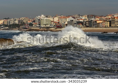 Waves breaking violently against rocks near the mouth of the Douro river, seeing in background all the coastal town of Porto in a stormy but sunny morning