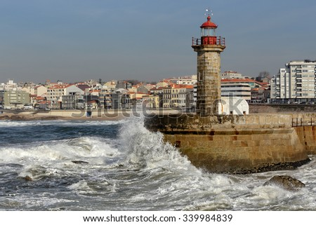 Waves breaking violently against rocks, pier and lighthouse of the Douro river mouth, seeing in background part of coastal town of Porto in a stormy but sunny morning - stock photo