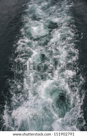 Waves caused by a ship at sea. - stock photo