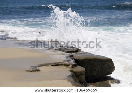 Waves crash against a rocky shore on the California coast.