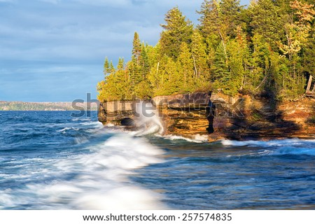 Waves crash along the shores of Lake Superior during a storm in the upper peninsula of Michigan. Pictured Rocks National Lakeshore. - stock photo