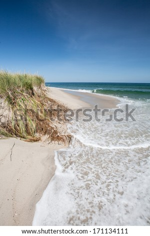 Waves crash on a Cape Cod beach during a sunny morning. Waves and wind, in association with sea level rise, are eroding many coastlines throughout the east coast and the world. - stock photo
