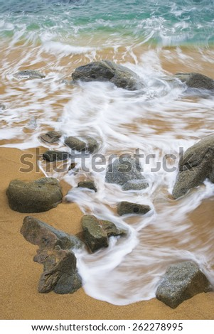 Waves crash onto a rocky, rugged coastline on an overcast morning. - stock photo