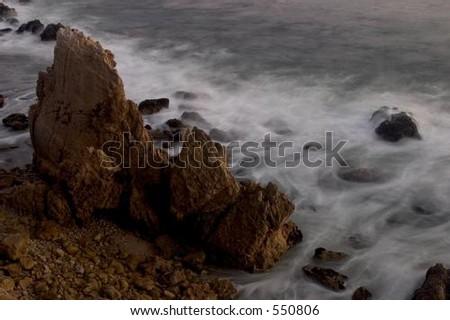 Waves crashing against coastline rocks - stock photo