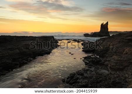 Waves crashing around Cathedral Rock at sunrise, south coast, NSW, Australia - stock photo