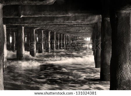 waves crashing in underneath the pier - stock photo
