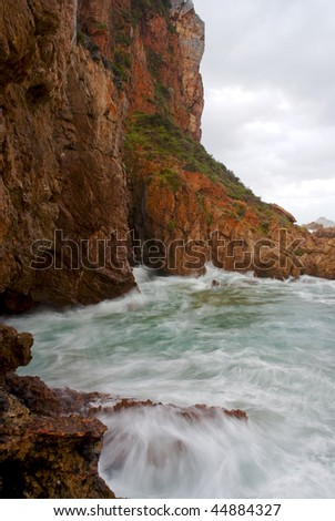 Waves crashing into cliffs protruding into the ocean with stormy clouds above - stock photo