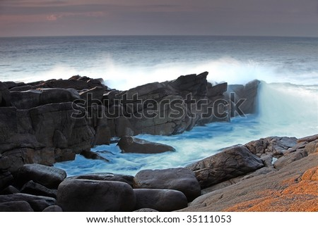 Waves crashing into the shore of Cape Spear in Newfoundland. - stock photo