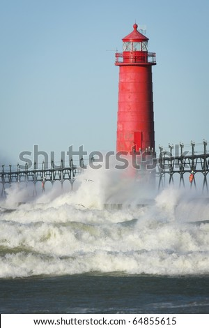 Waves crashing on lighthouse. Grand Haven lighthouse on Lake Michigan. Vertical format. - stock photo