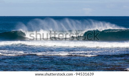 Waves crashing on reef of coast of Kauai and forming rainbow colors in the spray