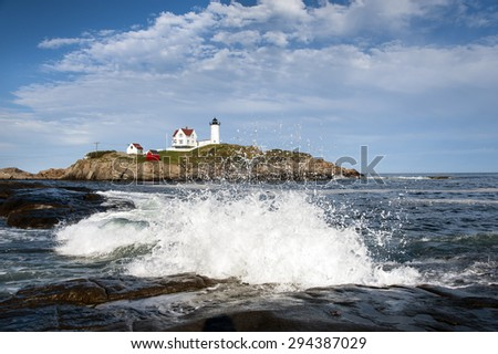Waves crashing on rocks by lighthouse in Maine. - stock photo