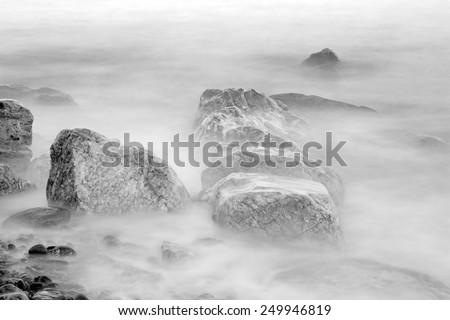 Waves crashing on the rocks - stock photo