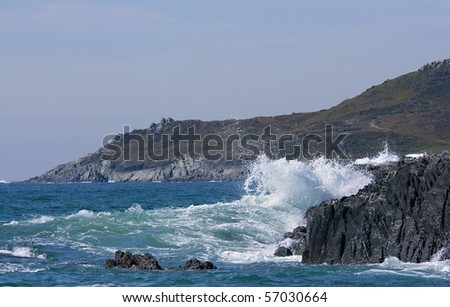 Waves crashing over a rocky headland - stock photo