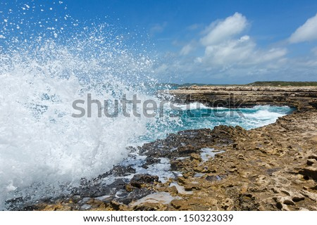 Waves Crashing over Devil's Bridge Coastline Antigua in Sunshine - stock photo