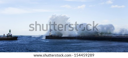 Waves crashing over lighthouse in Kalk Bay Harbour as fishermen brave storm, Cape Town, South Africa. - stock photo