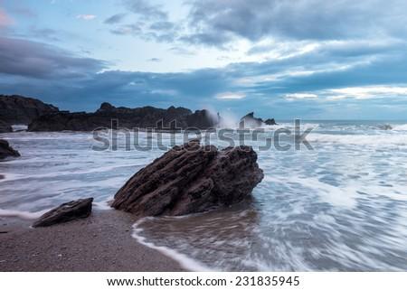Waves crashing over rocks at Whitsand Bay in Cornwall - stock photo
