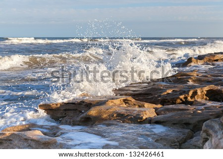 Waves crushing against a sandstone beach. - stock photo