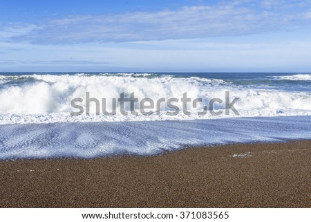 Waves crushing / breaking on a sandy beach making sea foam along the rugged Big Sur coastline, traveling the Big Sur Highway, on the California Central Coast, near Cambria CA. - stock photo