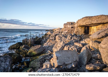 waves crushing over rocks and ruins of old fort at sunset on the beach