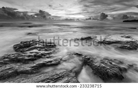 Waves Flow Hit the Rock During Sunrise in Black and White - stock photo