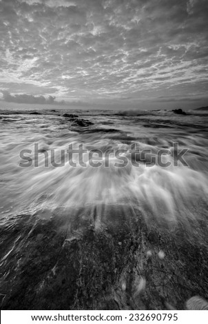 Waves Flow Hit the Rock In Black And White - stock photo
