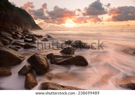 Waves flow over the rocky outcrop at Zenith Beach, Port Stephens during sunrise. - stock photo