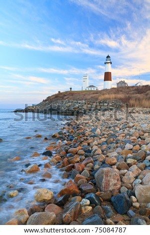 Waves from the Atlantic Ocean froth on the rocks below Montauk Lighthouse at the Eastern end of Long Island, New York - stock photo