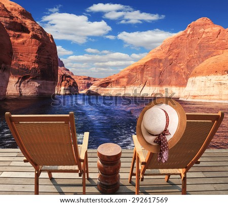 Waves from the boat cut through the Lake Powell on the Colorado River. At the stern of the vessel are two deck chairs. On the back of one hanging elegant ladies straw hat. - stock photo