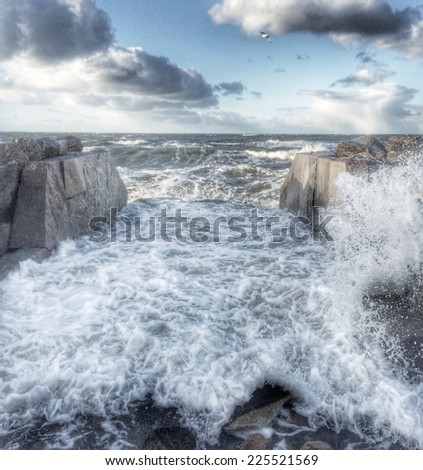 Waves from the sea breaking on a stone levy. - stock photo