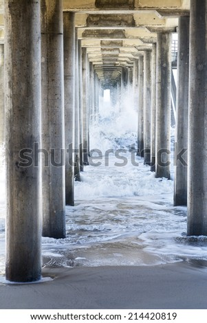 Waves generated by a storm rush through the underside of a pier, creating rough, turbulent water as it moves through the pillars to the beach. - stock photo