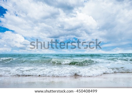 Waves in the ocean and sand on the beach - stock photo