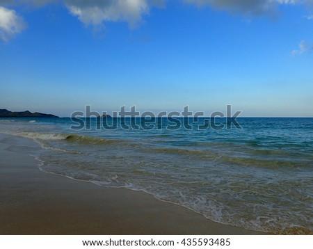 Waves lap on shore of Waimanalo Beach looking towards mokulua islands on Oahu, Hawaii. - stock photo