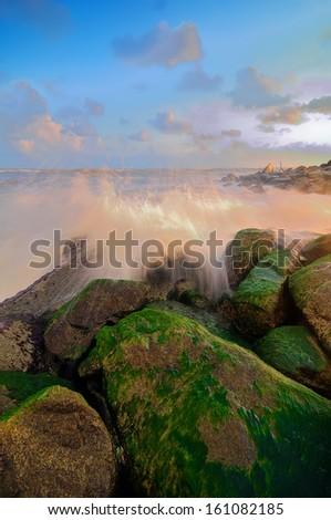 Waves lapping against rocks at Kuala Dasar Beach, Kelantan, Malaysia. Copy Space Area - stock photo