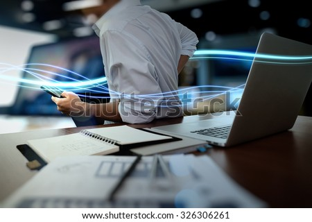 Waves of blue light and businessman using on smart phone and laptop computer as concept - stock photo