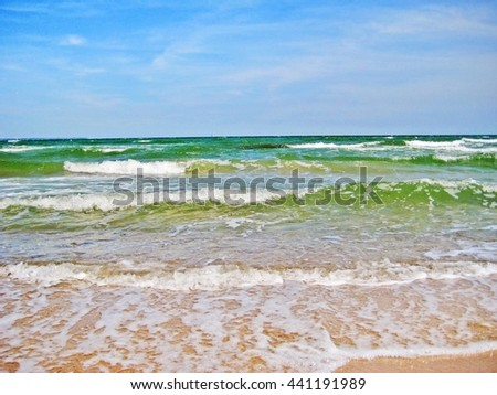 waves of the baltic sea ocean, beach in front, shore in the background, blue sky