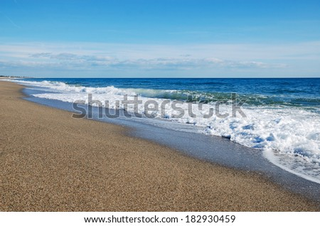 Waves of the blue sea surge in the sand beach. White foam glows between sandy coast and turquoise water surface reflecting azure sky. There is nobody. - stock photo