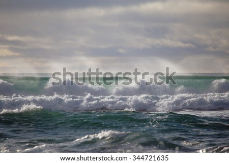 waves of the north atlantic ocean crashing on an icelandic beach after a storm - stock photo