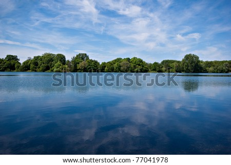 Waves on a lake under a blue sky. - stock photo