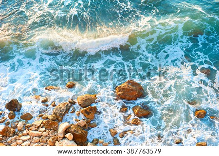 Waves on a rocky beach at sunset. Aerial view - stock photo